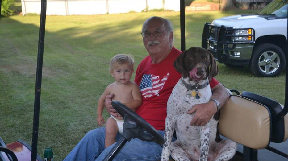 man, child and dog in golf cart